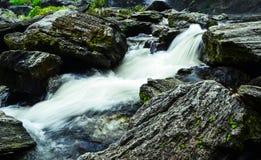 En ström som flödar ner från vattenfallet Arkivfoto