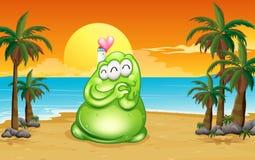 En strand med ett grönt monster Arkivbild
