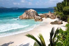 En strand med gömma i handflatan, stora stenar, turkosvatten och vågor royaltyfria bilder