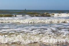 En strand med inkommande vågor och vitskum och en liten yacht på horisonten Royaltyfri Bild