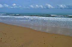En strand och moln Arkivbild
