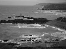 En strandsikt av havet och kusten i svartvitt Royaltyfria Bilder