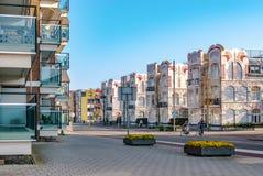 En streetview med moderna lägenheter på de vänstra och historiska jugendstilhusen på rätsida Två cyklar korsar gatan arkivfoto