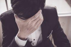 En stressad outaffärsman rymmer hans huvud royaltyfri fotografi