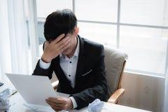 En stressad outaffärsman rymmer hans huvud i förtvivlan royaltyfri foto
