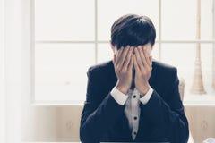 En stressad outaffärsman rymmer hans huvud i förtvivlan royaltyfria bilder