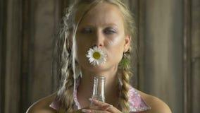 En strikt vegetariankvinna med kamomill i hennes mun arkivfilmer