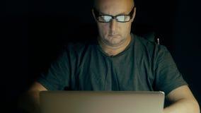 En student i exponeringsglas förbereder sig för examen på natten med en bärbar dator En man som surfar internet i sökande av info arkivfilmer