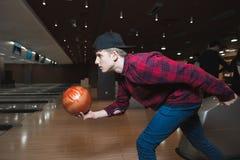 En student spelar bowling En ung man gör en bowlingballong att kasta Bowla på spåret Arkivbild