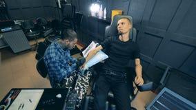 En studio med en manlig konstnär som gör en tatuering på mans prosthetic hand stock video