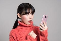 En studiostående av en asiatisk kvinna för tjugotal med en förvånad blick på telefonen Arkivfoton