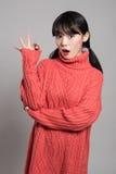 En studiostående av en asiatisk kvinna för tjugotal som pekar på något med ett finger och ser förvånad Royaltyfria Bilder