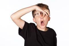 En studiostående på vit av en tonårs- pojke som rymmer hans näsa Royaltyfria Foton