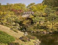 En stuga i en japansk trädgård med en flod royaltyfri foto
