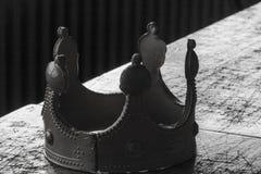 En stupad ledare: närbild av en tabell mycket av tuffa beslut och en sliten ut plast- guld- krona i svartvitt arkivfoton
