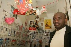 En sudanesisk flykting i hans mobiltelefon shoppar arkivbild