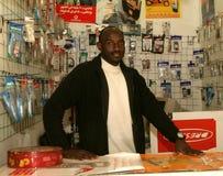 En sudanesisk flykting i hans mobiltelefon shoppar arkivfoton