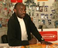 En sudanesisk flykting i hans mobiltelefon shoppar royaltyfri foto