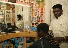 En sudanesisk flykting som arbetar i en barberare, shoppar royaltyfria foton