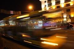 En suddig buss i gatan i aftonen Arkivfoto