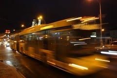 En suddig buss på avenyn i aftonen Arkivfoton