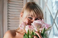 En suddig sikt av ett kvinnainnehav blommar av fönstret som ler fotografering för bildbyråer