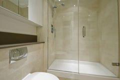 En-suite bathroom. Modern en-suite bathroom with floor to ceiling marble tiles Royalty Free Stock Image