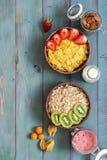 En sund frukost av sädesslag med jordgubbar och kiwin på en lantlig blå bakgrund Myslit och havreflingor, mjölkar, mandlar, berr arkivfoto