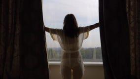 En Sunny Morning Happy Woman Opens las cortinas por la ventana en la casa almacen de video