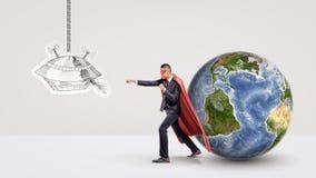 En superheroaffärsman som av slåss en pappers- teckning av en ufo medan bak honom ställningar ett litet jordjordklot Royaltyfria Foton