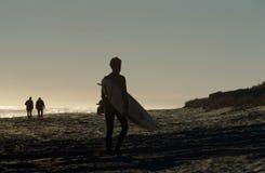 En surfare på en strand i Sydafrika. Arkivbild