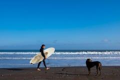 En surfare promenerar en Kalifornien strand Arkivfoton