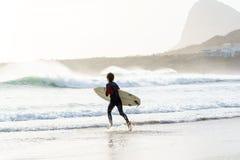 En surfarespring in i vattnet på stranden för fjärd för Betty ` s i den västra udden, Sydafrika royaltyfria bilder
