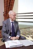 Hombre de negocios mayor que mira hacia fuera la ventana Fotos de archivo
