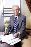 Hombre de negocios mayor que sonríe a la cámara Imagen de archivo libre de regalías