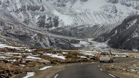 En SUV resande till och med de himalayan vägarna av norr Sikkim nära Gurudongmar sjön på 17000 ft höjd, Lachen, Sikkim, Indien Arkivbild
