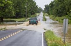 En SUV som kör på den översvämmade vägen Royaltyfri Bild