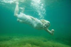 En sväva kvinna Undervattens- stående Flicka i vit klänningsimning i sjön Gröna flottaväxter, vatten royaltyfri foto