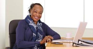 En svart affärskvinna poserar för en stående på hennes skrivbord Arkivfoto