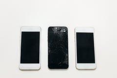 En svart bruten telefon och två vita hela nästa Royaltyfria Bilder