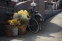 En svart gammal tappningcykel som kedjas fast till en skeppsdockapol med påsar på sidan Royaltyfri Fotografi