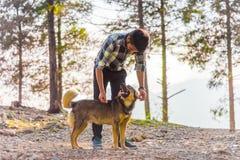 En svart haired man som spelar med hans hund arkivfoto