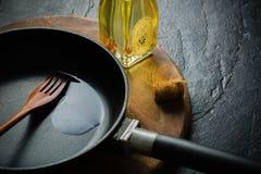 En svart järn- stekpanna för att laga mat mat olja kryddar grönsaken Fotografering för Bildbyråer