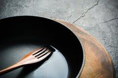 En svart järn- stekpanna för att laga mat mat olja kryddar grönsaken Royaltyfria Bilder