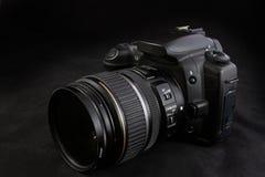 En svart kamera med zoomobjektivet som isoleras på svart bakgrund Fotografering för Bildbyråer