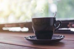 En svart kopp av varmt kaffe med att ånga på trätabellen Arkivfoto