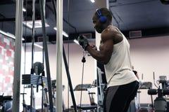 En svart muskulös man i en T-tröja och hörlurar skakar hans händer med en simulator i idrottshallen arkivfoton