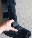 En svart en ortopediskt eller medicinsk känga, ensemble eller skodon royaltyfri foto