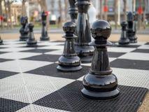 En svart schackuppsättning in på ett jätte- schackbräde royaltyfria foton