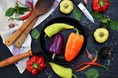 En svart stekpanna med olika variationer av söta och varma peppar på mörk träbakgrund Förberedelse av ragu eller att steka Co Fotografering för Bildbyråer
